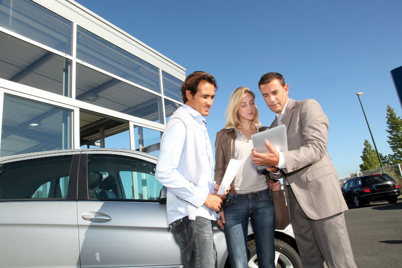 Customers and car sales person